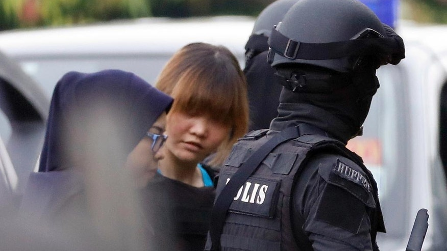 Vietnamese suspect Doan Thi Huong, center, arrested in the death of Kim Jong Nam, is escorted by police officers as she arrives at a court house in Sepang, Malaysia, Thursday, April 13, 2017. Malaysian authorities said the two women swiped Kim's face with VX nerve agent as he waited in Kuala Lumpur airport for a flight home to Macau in February. (AP Photo/Vincent Thian)