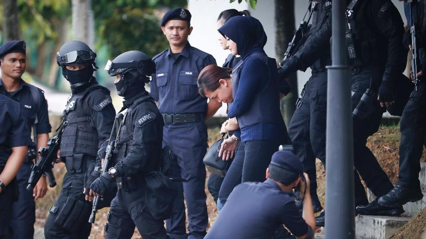 Indonesian suspect Siti Aisyah, center, arrested in the death of Kim Jong Nam, is escorted by police officers as she leaves a court house in Sepang, Malaysia, Thursday, April 13, 2017. Malaysian authorities said two women swiped Kim's face with VX nerve agent as he waited in Kuala Lumpur airport for a flight home to Macau in February. (AP Photo/Vincent Thian)