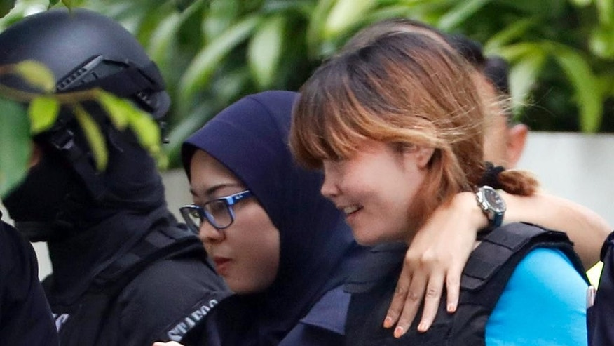 Vietnamese suspect Doan Thi Huong, right, arrested in the death of Kim Jong Nam, is escorted by police officers as she leaves a court house in Sepang, Malaysia, Thursday, April 13, 2017. Malaysian authorities said two women swiped Kim's face with VX nerve agent as he waited in Kuala Lumpur airport for a flight home to Macau in February. (AP Photo/Vincent Thian)