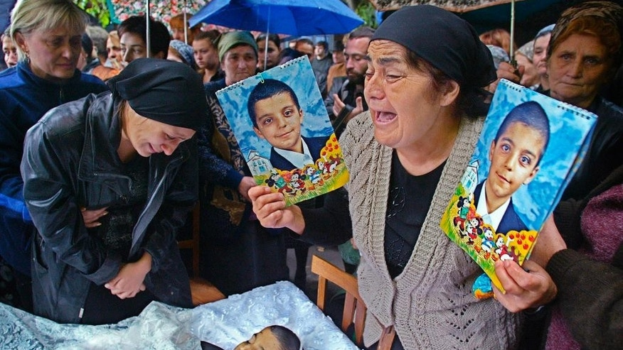 FILE - In this Monday, Sept. 6, 2004 file photo Fedosya Beroyeva, grand mother of 10-year old twins, Soslan, right, and Aslan, killed in the school hostage taking, cries holding their portraits as their mother Zalina, left, looks at Aslan's body during the twins' funeral in Beslan, Russia. The European Court of Human Rights said  Thursday, April 13, 2017, that Russia failed to adequately protect victims of a 2004 school siege in the city of Beslan that left more than 300 people dead.   (AP Photo/Sergey Ponomarev, File)