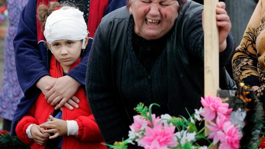 FILE In this Friday, Sept. 10, 2004 file photo Alina, 7, left, injured during the school siege in Beslan that ended with the deaths of at least 330 hostages, mourns together with her relatives for her 12-year-old brother Akhsarbek Tskayev, who was killed in the incident, in a cemetery in Beslan, Russia. The European Court of Human Rights said  Thursday, April 13, 2017, that Russia failed to adequately protect victims of a 2004 school siege in the city of Beslan that left more than 300 people dead.  (AP Photo/Alexander Zemlianichenko, File)