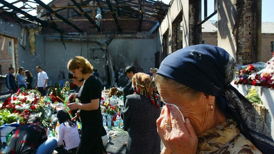 FILE - In this Thursday, Sept. 9, 2004 file photo an elderly woman cries in a ruined gym in the school, scene of the hostage crisis, in Beslan, Russia. The European Court of Human Rights said  Thursday, April 13, 2017, that Russia failed to adequately protect victims of a 2004 school siege in the city of Beslan that left more than 300 people dead.   (AP Photo/Alexander Zemlianichenko, File)