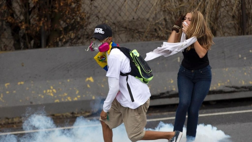 Demonstrator stand in a cloud of tear gas launched by Bolivarian National Guard soldiers during an anti-government protest in Caracas, Venezuela, Thursday, April 13, 2017. Venezuela officials are confirming that a fifth person has died in a two-week old anti-government protest movement. (AP Photo/Ariana Cubillos)
