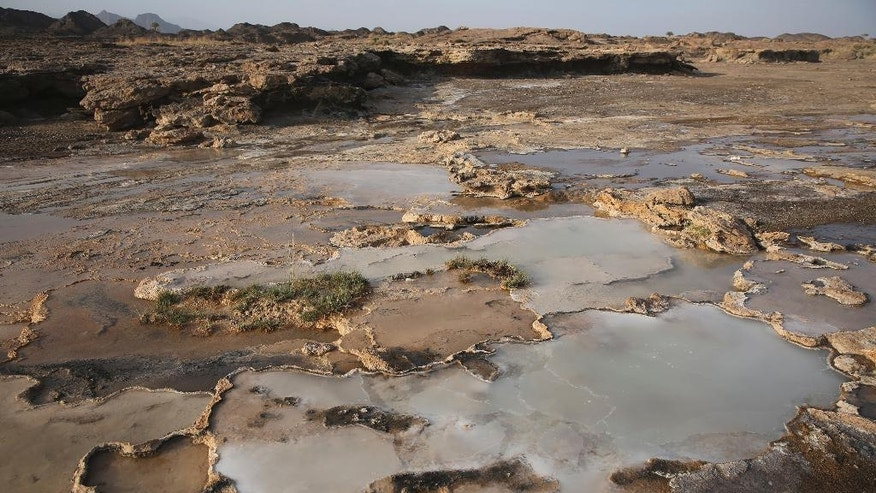 This March 5, 2017 photo shows travertine pools with white films of carbon fused with calcium, a chemical process being explored by a geological research project, in the al-Hajjar mountains of Oman. Deep in the jagged red mountains, geologists from the Oman Drilling Project are drilling in search of the holy grail of reversing climate change: an efficient and cheap way to remove carbon dioxide from the air and oceans. They are coring samples from one of the world's only exposed sections of the Earth's mantle to uncover how a spontaneous natural process millions of years ago transformed CO2 into limestone and marble. (AP Photo/Sam McNeil)