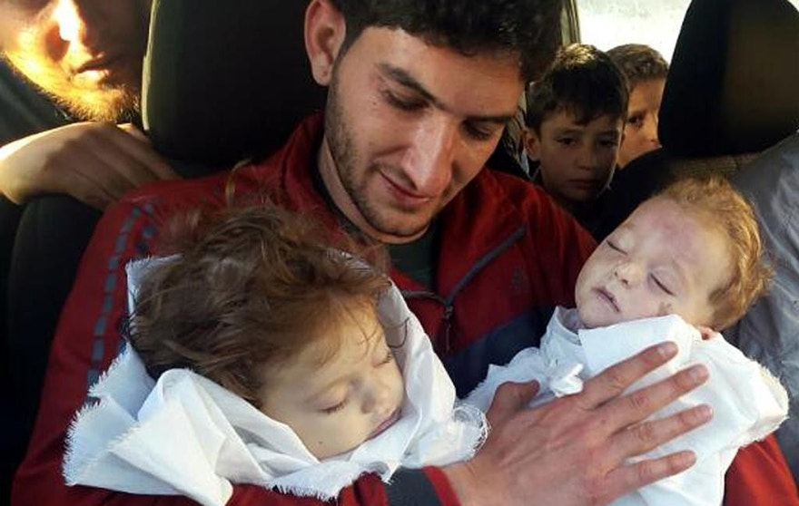 In this picture taken on Tuesday April 4, 2017, Abdul-Hamid Alyousef, 29, holds his twin babies who were killed during a suspected chemical weapons attack, in Khan Sheikhoun in the northern province of Idlib, Syria. Alyousef also lost his wife, two brothers, nephews and many other family members in the attack that claimed scores of his relatives. The death toll from a suspected chemical attack on a northern Syrian town rose to 72 on Wednesday as activists and rescue workers found more terrified survivors hiding in shelters near the site of the harrowing assault, one of the deadliest in Syria's civil war. (Alaa Alyousef via AP)