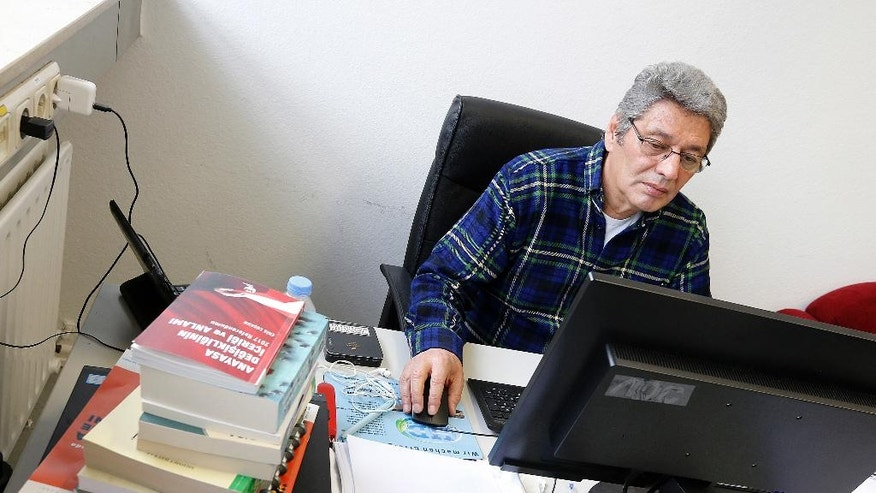 In this April 11, 2017 photo Arti TV editor-in-chief Celal Baslangic works at his computer in the studio in Cologne, Germany. Baslangic wants to bring fact-based reporting to Turks in Turkey and in Germany. (AP Photo/Michael Probst)