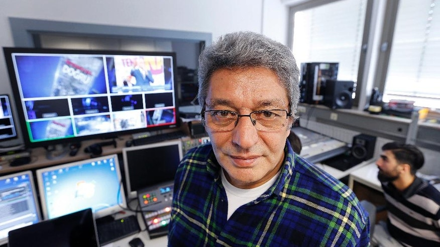 In this April 11, 2017 photo Arti TV editor-in-chief Celal Baslangic poses in the studio in Cologne, Germany. Bsalnagic wants to bring fact-based reporting to Turks in Turkey and in Germany. (AP Photo/Michael Probst)