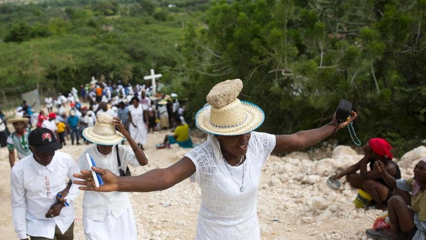 A woman stretches out her arms in prayer as balances a stone on her head as a form of penance during a Good Friday ritual, in Ganthier, Haiti, Friday, April 14, 2017. Thousands of Haitians flock to mount Calvaire Miracle with rocks balanced on their heads, to pray and seek renewal in one of the spiritually-steeped country's biggest annual pilgrimages. ( AP Photo/Dieu Nalio Chery)