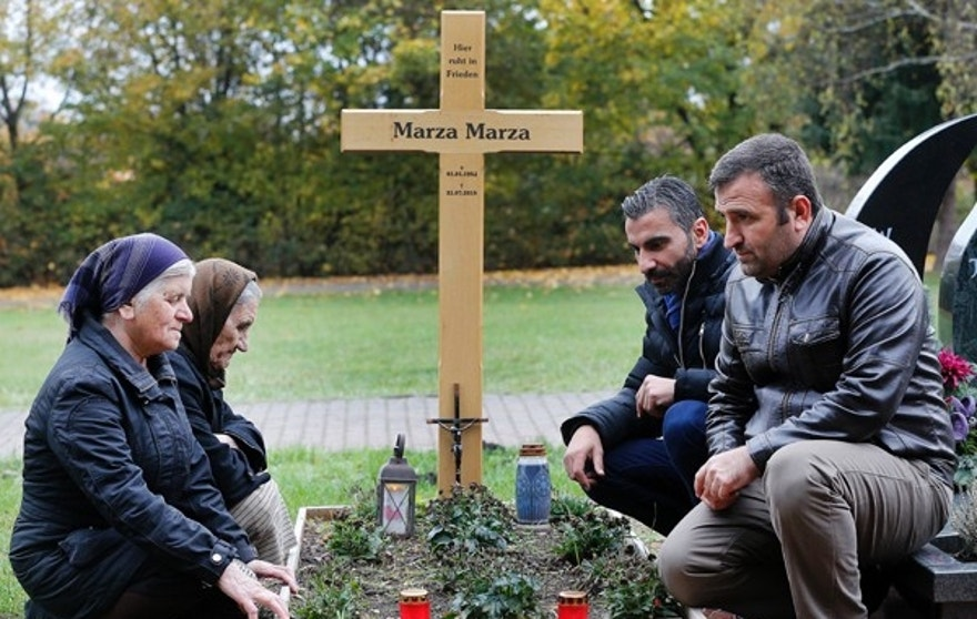 Zammo Marza, Sherineh Marza, Charli Kanoun and Abdo Marza, from left, kneel at the grave of Marza Marza in Saarlouis, Germany in this Monday, Nov. 7, 2016 photo. The Marza family were among 226 Assyrian Christians taken captive by the Islamic State group in a February 2015 attack on their villages in Syria's Khabur River valley. It took a year to free the hostages, and only after three were killed and millions of dollars gathered by the Assyrian diaspora worldwide was paid to the militants, and in the end the Khabur region has been totally emptied of the tiny, centuries-old minority community. (AP Photo/Michael Probst)
