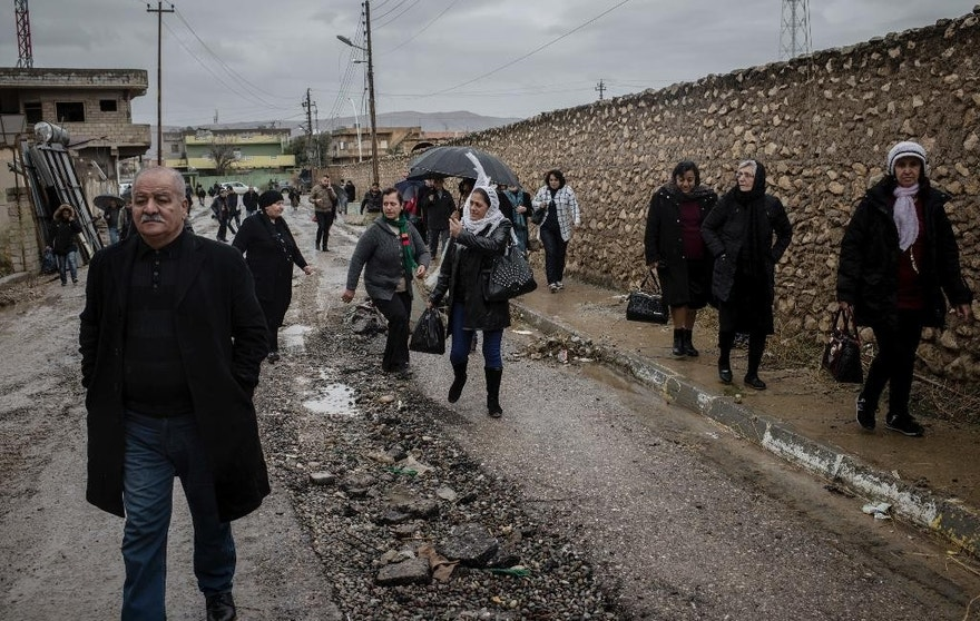 Christians walk in the rain to attend Christmas Eve's Mass in the Assyrian Orthodox church of Mart Shmoni, in Bartella, Iraq, Saturday, December 24, 2016. For the 300 Christians who braved rain and wind to attend the mass in their hometown, the ceremony provided them with as much holiday cheer as grim reminders of the war still raging on around their northern Iraqi town and the distant prospect of moving back home. Displaced when the Islamic State seized their town in 2014, they were bused into the town from Irbil, capital of the self-ruled Kurdish region, where they have lived for more than two years. (AP Photo/Cengiz Yar)
