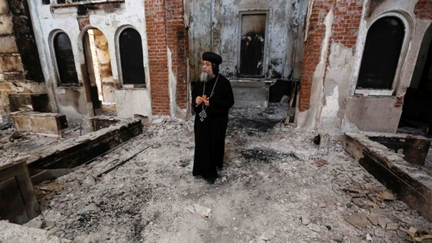 A Coptic Orthodox bishop surveys a damaged church in late August in Minya, Egypt. Concelebrating Mass with the leader of Egypt's Coptic Catholics, Pope Francis prayed for the safety and religious liberty of Christians in the Middle East. (CNS photo/Louafi Larbi, Reuters) (Dec. 9, 2013) See POPE-COPTS Dec. 9, 2013.