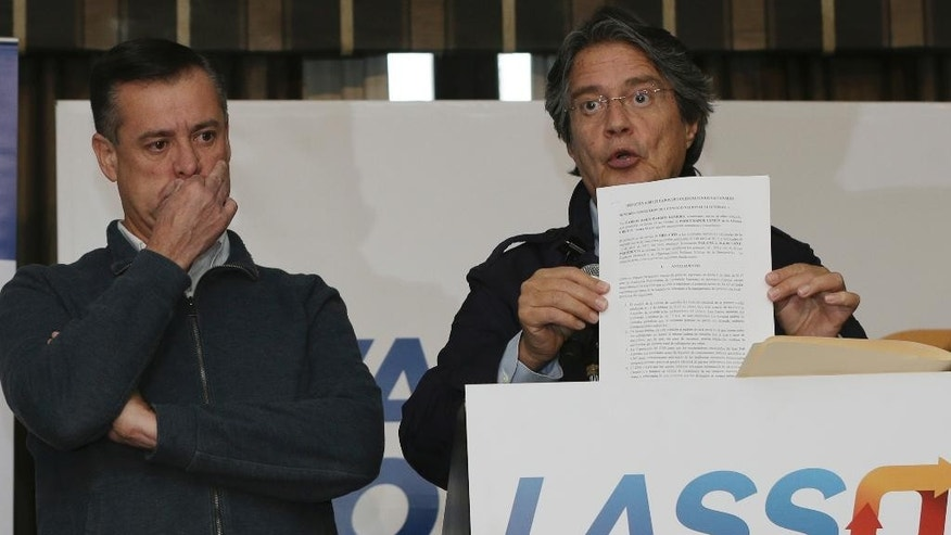 Guillermo Lasso, the opposition candidate defeated in the elections of April 2, shows a document during a press conference at Dan Carlton hotel in Quito, Ecuador, Wednesday, April 12, 2017. Lasso is demanding a recount claiming irregularities during the recent runoff presidential elections. (AP Photo/Dolores Ochoa)