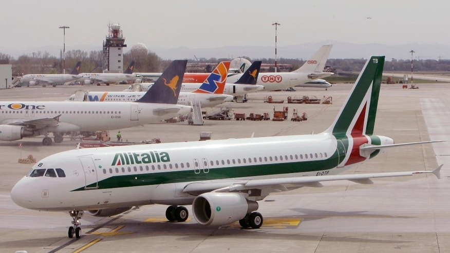 FILE - In this March 25, 2009 file photo, an Alitalia Airbus A320 is seen at the Linate airport in Milan. Premier Paolo Gentiloni urged Alitalia workers on Friday to approve a compromise deal to relaunch Italy's struggling flagship airline that was reached in last-ditch, government-mediated negotiations between unions and Alitalia management. (AP Photo/Antonio Calanni)