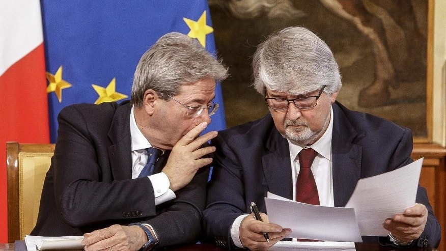 Italian Premier Paolo Gentiloni, left, and Italian Labour Minister Giuliano Poletti talk during a press conference at Chigi Palace in Rome, Italy, Friday,  April 14, 2017. Gentiloni urged Alitalia workers on Friday to approve a compromise deal to relaunch Italy's struggling flagship airline that was reached in last-ditch, government-mediated negotiations between unions and Alitalia management.  (Giuseppe Lami/ANSA via AP)