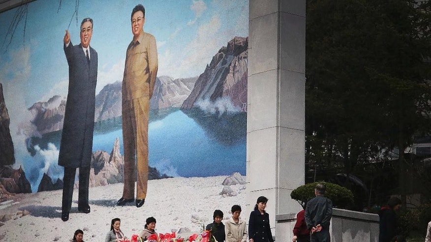 North Koreans offer flowers in front of a mural of late leaders Kim Il Sung, left, and Kim Jong Il on Friday, April 14, 2017, in Pyongyang, North Korea. Amid rising regional tensions, Pyongyang residents have been preparing for North Korea's most important holiday: the 105th birth anniversary of Kim Il Sung, the country's late founder and grandfather of current ruler Kim Jong Un. (AP Photo/Wong Maye-E)
