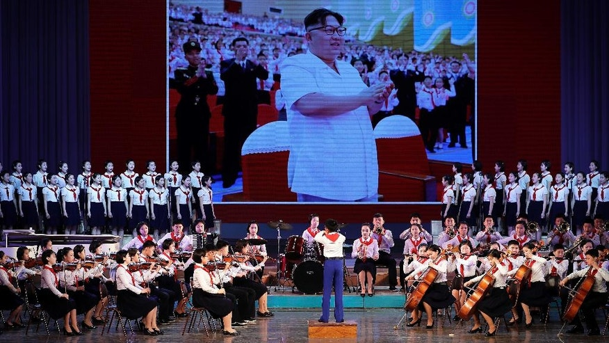 North Korean school children perform at the Mangyongdae Children's Palace while an image of their leader Kim Jong Un is projected on a screen Friday, April 14, 2017, in Pyongyang, North Korea. Amid rising regional tensions, Pyongyang residents have been preparing for North Korea's most important holiday: the 105th birth anniversary of Kim Il Sung, the country's late founder and grandfather of current ruler Kim Jong Un. (AP Photo/Wong Maye-E)