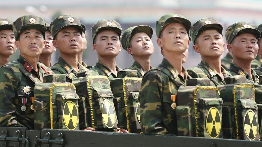 "In this July 27, 2013, file photo, North Korean soldiers turn and look towards leader Kim Jong Un as they carry packs marked with the nuclear symbol at a parade in Pyongyang, North Korea. North Korea's vice foreign minister Han Song Ryol said in an interview with the Associated Press on Friday, April 14, 2017: ""We've got a powerful nuclear deterrent already in our hands, and we certainly will not keep our arms crossed in the face of a U.S. pre-emptive strike."" (AP Photo/Wong Maye-E, File)"