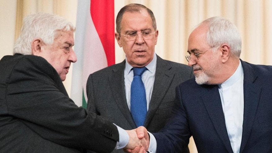Russian Foreign Minister Sergey Lavrov, center, stands in the middle as Syrian Foreign Minister Walid Muallem, left, and Iranian Foreign Minister Mohammad Javad Zarif shake hands after a shared press conference following their talks focused on Syria in Moscow, Russia, Friday, April 14, 2017. (AP Photo/Pavel Golovkin)