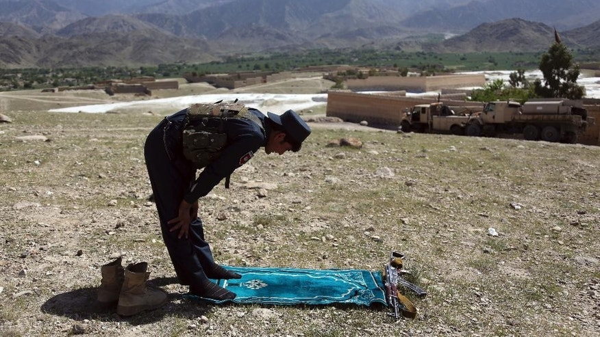 An Afghan security personnel prays in Pandola village near the site of a U.S. bombing in the Achin district of Jalalabad, east of Kabul, Afghanistan, Friday, April 14, 2017. U.S. forces in Afghanistan on Thursday struck an Islamic State tunnel complex in eastern Afghanistan with the largest non-nuclear weapon every used in combat by the U.S. military, Pentagon officials said. (AP Photo/Rahmat Gul)
