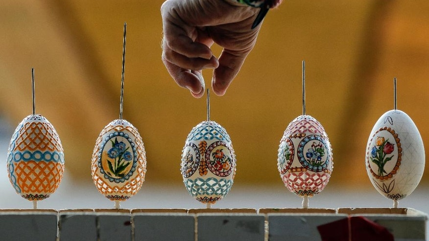 In this Thursday, April 13, 2017, picture artisan Nicu Poenariu turns Easter eggs on sale at a fair in Bucharest, Romania. Ahead of Easter, celebrated by both Orthodox and Catholic believers on April 16 processions of priests clad in golden robes carrying foliage on Palm Sunday in a recreation of Jesus' ride into Jerusalem, mixed with more commercial flavored celebrations like an Easter fair outside the giant palace built by late Communist leader Nicolae Ceausescu where entertainers strutted around wearing giant rabbit heads.(AP Photo/Vadim Ghirda)