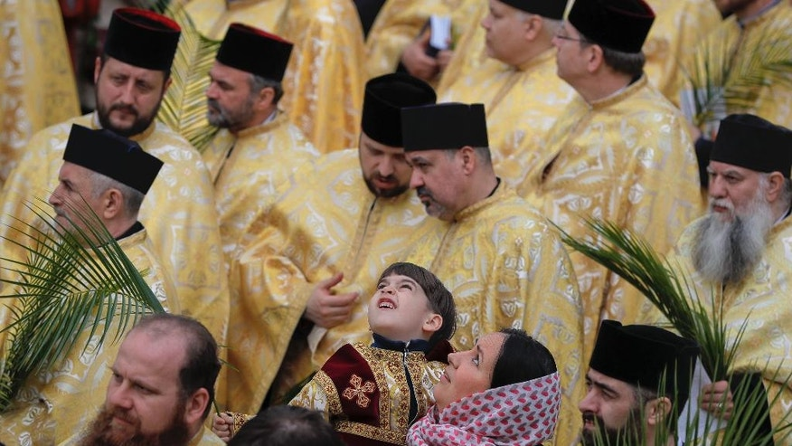 In this Saturday, April 8, 2017, picture a Romanian Orthodox priest's son looks up along with his mother during a service ahead of Palm Sunday in Bucharest, Romania. Ahead of Easter, celebrated by both Orthodox and Catholic believers on April 16 processions of priests clad in golden robes carrying foliage on Palm Sunday in a recreation of Jesus' ride into Jerusalem, mixed with more commercial flavored celebrations like an Easter fair outside the giant palace built by late Communist leader Nicolae Ceausescu where entertainers strutted around wearing giant rabbit heads.(AP Photo/Vadim Ghirda)