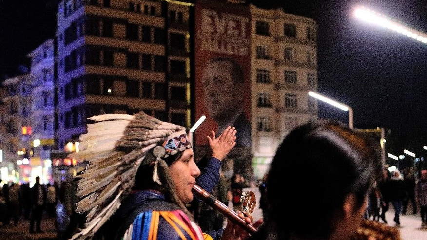 Musicians from a Latin American band perform at the Taksim square with a giant poster of Turkey's President Recep Tayyip Erdogan in the background, ahead of the upcoming referendum, at Taksim square in Istanbul, Friday, April 14, 2017. Turkey is heading to an April 16 contentious referendum on constitutional reforms to expand Turkey's President Recep Tayyip Erdogan's powers. (AP Photo/Petros Karadjias)