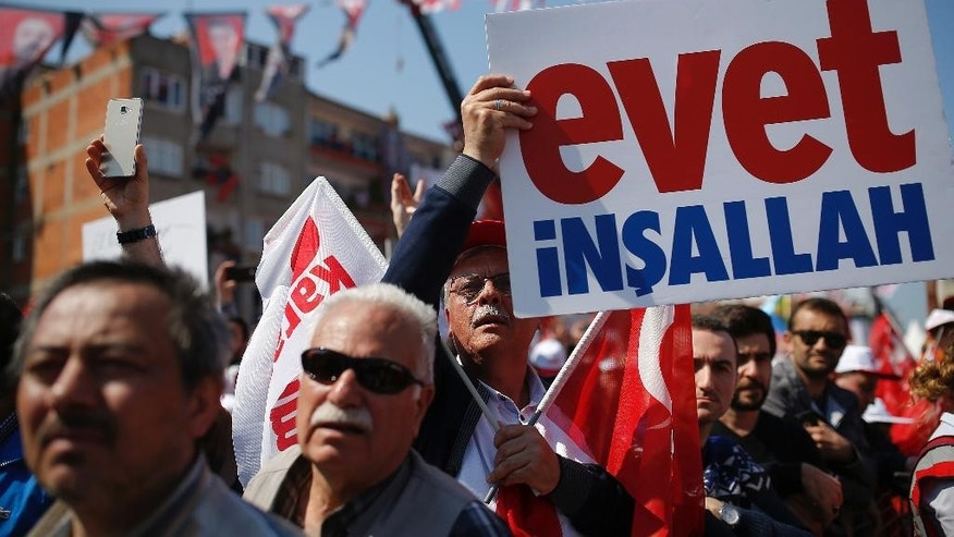 "Supporters hold a placard that reads ""Yes God willing"" as they listen to Turkey's President Recep Tayyip Erdogan during a last referendum rally in Istanbul's Umraniye district, Saturday, April 15, 2017. Campaigning for Turkey's crucial referendum on whether to expand presidential powers has entered its final stretch, with President Recep Tayyip Erdogan addressing flag-waving supporters in an Istanbul neighborhood to drum up support for his ""yes"" campaign.(AP Photo/Emrah Gurel)"