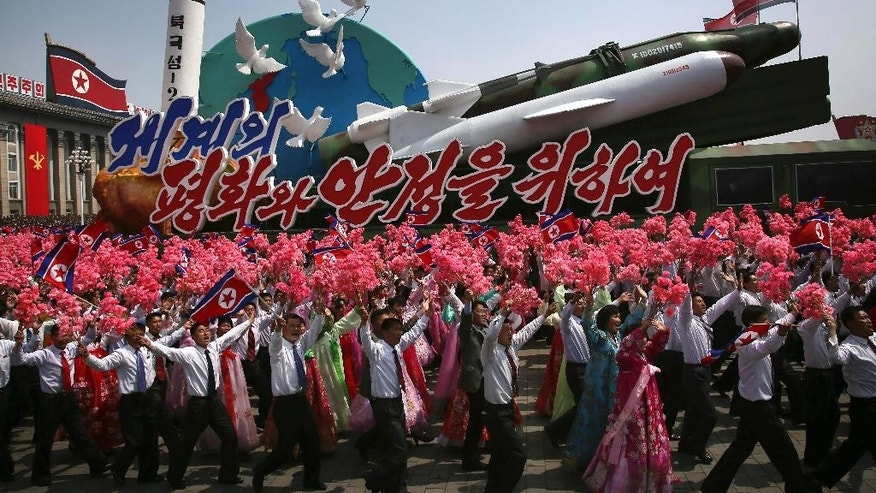 "FILE - In this Saturday, April 15, 2017 file photo, North Korean men and women wave flags and plastic flowers as a float with model missiles and rockets with words that read ""For Peace and Stability in the World"" is paraded across Kim Il Sung Square during a military parade in Pyongyang. North Korea on Sunday, April 16, failed in a missile launch from its eastern coast, South Korea's Joint Chiefs of Staff said, but it wasn't immediately clear what kind of missile was fired. The launch from the city of Sinpo comes a day after one of the biggest North Korean propaganda events of the year— celebrations of the 105th birthday of late North Korea founder Kim Il Sung, the current leader's grandfather. (AP Photo/Wong Maye-E, File)"