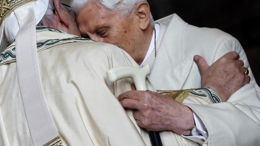 "FILE - In this Tuesday, Dec. 8, 2015 file photo, Pope Emeritus Benedict XVI, right, hugs Pope Francis in St. Peter's Basilica during the ceremony marking the start of the Holy Year, at the Vatican. A ""modest"" 90th birthday party is being planned for Benedict XVI, who stunned the Catholic church by resigning in 2013. His aide, Monsignor Georg Gaenswein, says Benedict's birthday, which falls on Easter Sunday this year, will be celebrated on Monday in Bavarian style in keeping with the emeritus pontiff's roots. (AP Photo/Gregorio Borgia, File)"