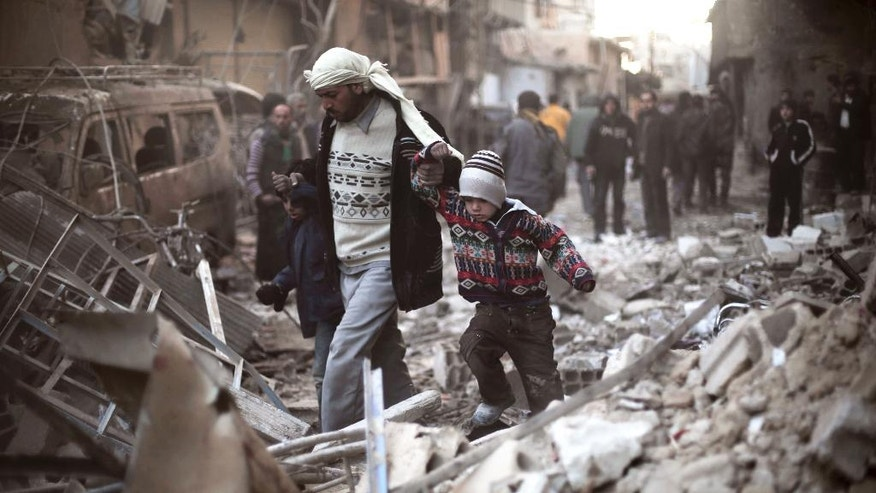 FILE - This Dec. 24, 2015 file photo provided by Save the Children, a man walks with a pair of children in hand hand through the rubble in Eastern Ghouta, Syria. Warplanes conducted more than 70 airstrikes in one day on rebel-held neighborhoods of the Syrian capital Damascus and its eastern suburbs killing dozens of people while artillery and tanks pounded the areas giving cover to troops and pro-government gunmen as the marched in one of their deepest incursions into the areas in years. (Save the Children via AP, File)
