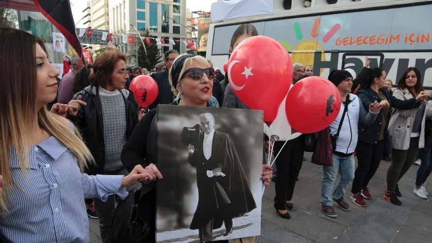 "A supporter of the ""NO"" campaign holding a poster of Turkey's founder Kemal Ataturk, dances with others during a gathering ahead of the Sunday referendum, in Ankara, Turkey, Friday, April 14, 2017. Turkey is heading to a contentious April 16 referendum on constitutional reforms to expand President Recep Tayyip Erdogan's powers. (AP Photo/Burhan Ozbilici)"