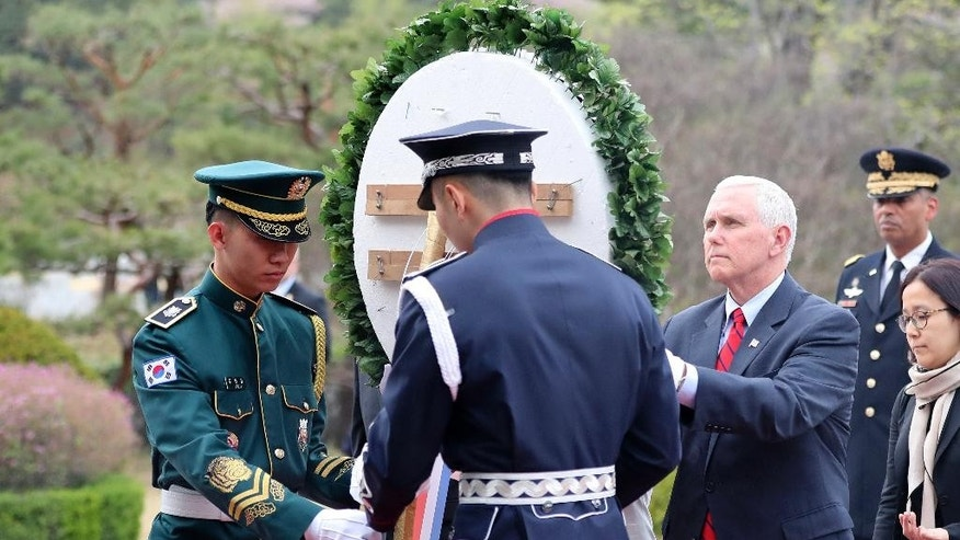 U.S. Vice President Mike Pence, center, lays a wreath at the Seoul National Cemetery in Seoul, South Korea, Sunday, April 16, 2017. Pence arrived in South Korea on Sunday to begin a 10-day trip to Asia that comes amid turmoil on the Korean Peninsula over North Korea's threats to advance its nuclear and defense capabilities, and just after a failed missile launch by the North. (AP Photo/Lee Jin-man)