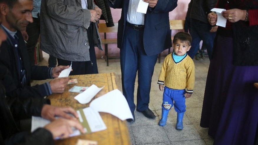A boy stands amid voters inside a polling station in Diyarbakir, southeastern Turkey, on Sunday, April 16, 2017. Voters in Turkey were deciding Sunday on the future of their country, with polling stations opening for a historic referendum, which was called by President Recep Tayyip Erdogan, on whether to approve reforms that would concentrate power in the hands of the president. (AP Photo/Emre Tazegul)
