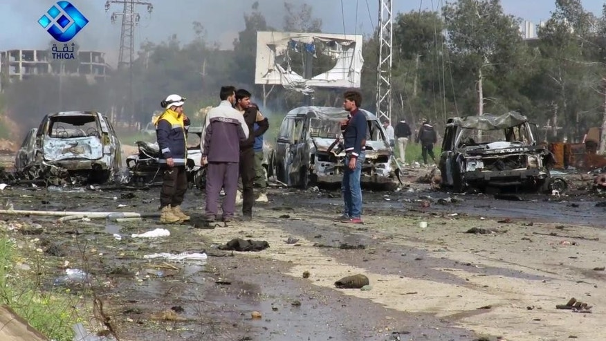 This frame grab from video provided by the Thiqa News Agency, shows rebel gunmen at the site of a blast that damaged several buses and vans at the Rashideen area, a rebel-controlled district outside Aleppo city, Syria, Saturday, April. 15, 2017. Syrian TV said at least 39 people were killed Saturday in an explosion that hit near buses carrying evacuees from two towns besieged by rebels nearby. (Thiqa News via AP)