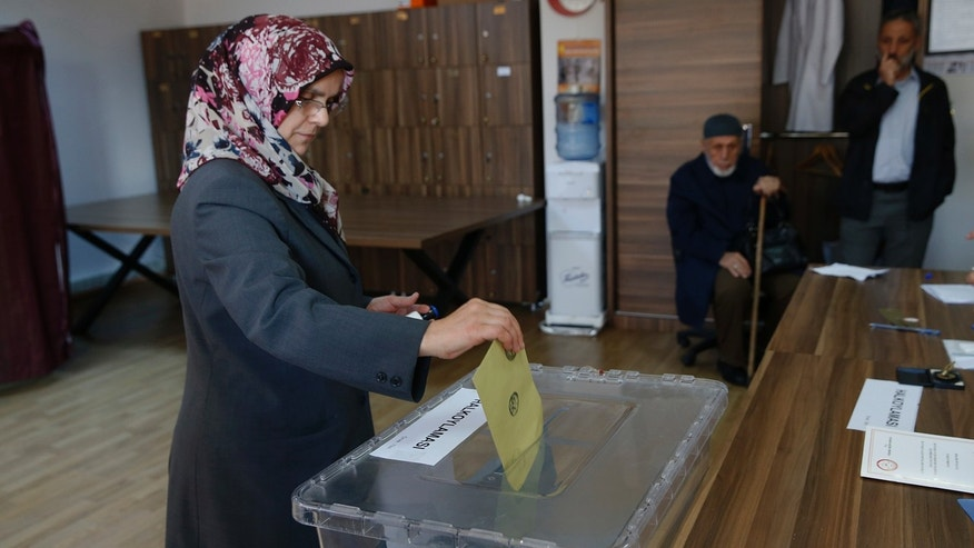 A woman casts a ballot inside a polling station in Istanbul, Sunday, April 16, 2017.