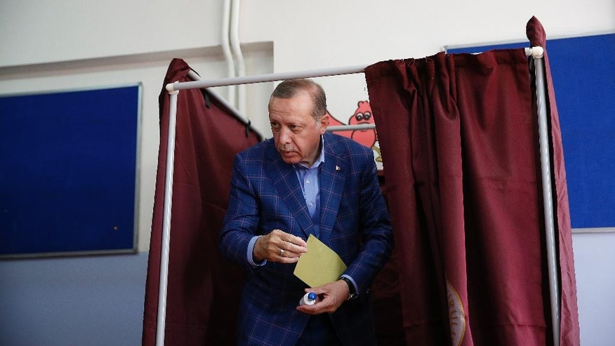 Turkey's President Recep Tayyip Erdogan leaves a voting booth inside a polling station in Istanbul, Turkey, on Sunday, April 16, 2017. Voters in Turkey were casting their ballots Sunday in a historic referendum to approve or reject a set of constitutional reforms that would greatly expand the president's powers. (AP Photo/Lefteris Pitarakis)