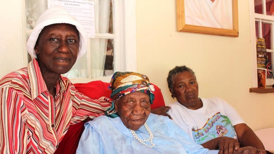 The world's oldest person Violet Brown, center, poses with her care givers Elaine Mcgrowder , left, and Dolet Grant at her home in Duanvale district of Trelawny, Jamaica, Sunday, April 16, 2017. The 117-year-old woman living in the hills of western Jamaica  is believed to have become the world's oldest person, according to groups that monitor human longevity. (AP Photo/Raymond Simpson)