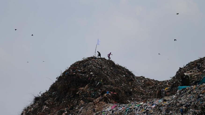 Sri Lankan men walk back after erecting a white flag on top of a garbage mound following the garbage dump collapse in Meetotamulla, on the outskirts of Colombo, Sri Lanka, Sunday, April 16, 2017. The death toll from the collapse of the massive garbage mound near Sri Lanka's capital rose to more than a dozen Sunday, and residents feared more victims could be buried underneath the debris. Maj. Gen. Sudantha Ranasinghe, who is heading the rescue efforts, said 78 houses were destroyed and more than 150 were damaged. (AP Photo/Eranga Jayawardena)