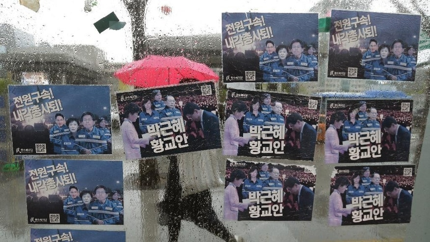 "Posters showing portraits of former South Korean President Park Geun-hye, her aides and business men close to her are pasted on a glass at an underground entrance in Seoul, South Korea, Monday, April 17, 2017. South Korean prosecutors on Monday indicted Park on high-profile corruption charges that could potentially send her to jail for life. The signs read ""Arrest."" (AP Photo/Ahn Young-joon)"