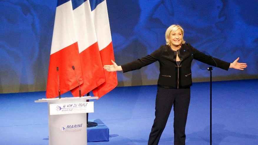 FILE - In this Feb.5, 2017 file photo, French far-right leader presidential candidate Marine Le Pen acknowledges applause in Lyon, central France. Do voters judge a book by its cover? France's presidential candidates certainly think they do, and more than ever are trying to get their political message across through their wardrobes, from centrist Emmanuel Macron's regular-guy suits to far right leader Marine Le Pen's masculine dark wardrobe and hard-left Jean-Luc Melenchon's communist-inspired jackets. (AP Photo/Michel Euler, File)