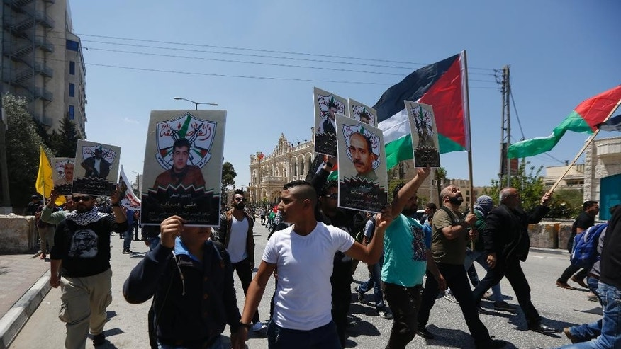 People hold posters of imprisoned during a rally in support of Palestinian prisoners in the West bank City of Bethlehem, Monday, April 17, 2017. An activist said more than 1,500 Palestinian prisoners have launched an open-ended hunger strike to demand better conditions in Israeli prisons, including more contact with relatives, and an end to Israel's practice of detentions without trial. (AP Photo/Majdi Mohammed)