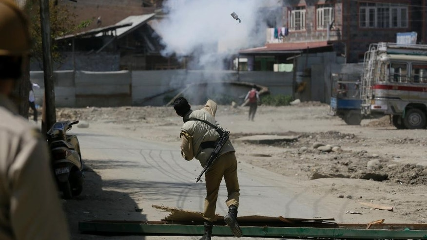An Indian policeman throws tear smoke shell on protesting Kashmiri students as they clash in Srinagar, Indian controlled Kashmir, Monday, April 17, 2017. The clashes on Monday began in Srinagar when hundreds of college students took to the streets to protest a police raid in a college in southern Pulwama town over the weekend, in which at least 50 students were injured. (AP Photo/Mukhtar Khan)