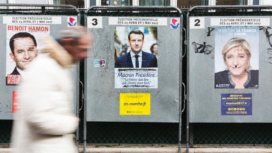 A man walks past electoral posters displaying the presidential candidates, Benoit Hamon, left, Emmanuel Macron, center, and Marine Le Pen in Paris, France, Monday, April 17, 2017. French centrist candidate Emmanuel Macron and far-right leader Marine Le Pen are hoping to bring in big crowds at competing rallies in Paris as the unpredictable race nears its finish. (AP Photo/Kamil Zihnioglu)