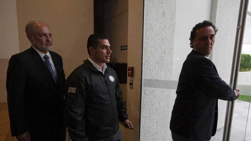 Alberto Elias Beltran, right, and Omar Garcia Harfuch, center, of Mexico's Federal Attorney General's Office, and Mexican embassy staffer Angel Dominguez leave after a press conference at the Mexican embassy in Guatemala City, Sunday, April 16, 2017. Mexico's former Veracruz state Gov. Javier Duarte, who is accused of running a ring that allegedly pilfered from state coffers, has been detained in Guatemala after six months as a fugitive and a high-profile symbol of government corruption. (AP Photo/Moises Castillo)