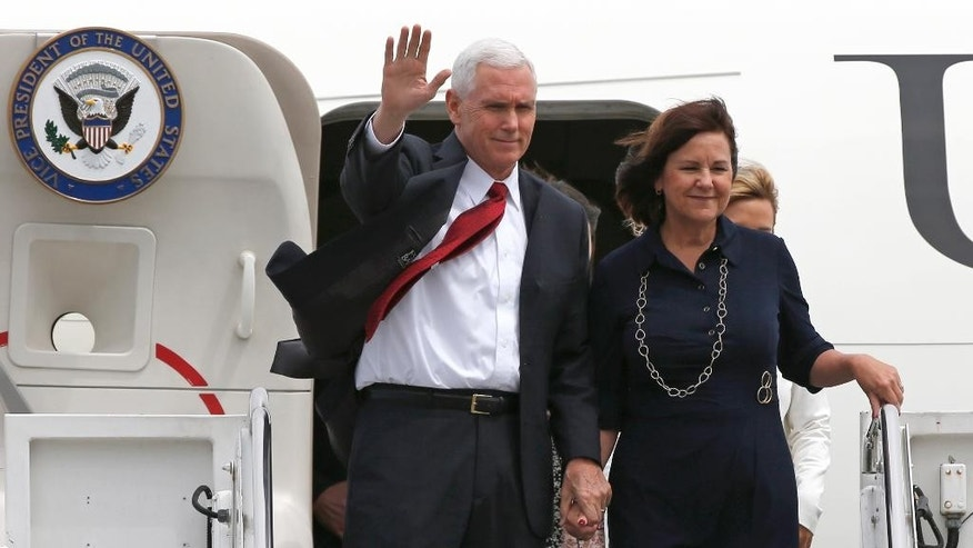 CORRECTS DAY OF WEEK AND UPDATE SECOND SENTENCE - U.S. Vice President Mike Pence, left, waves with his wife Karen on their arrival at U.S. Navy's Atsugi air facility in Ayase, southwest of Tokyo, Tuesday, April 18, 2017. Pence arrived in Japan for talks Tuesday expected to focus largely on trade with America's anchor ally in the region. (AP Photo/Shuji Kajiyama)