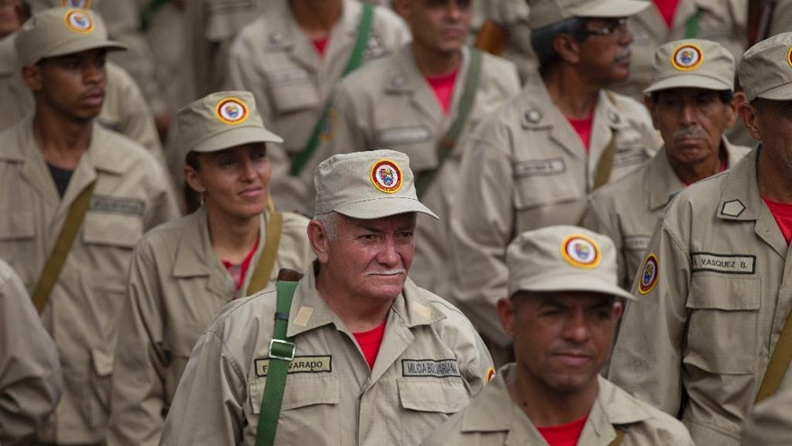 Members of the Bolivarian Militia march during their seventh anniversary celebration, in front of the Miraflores presidential palace in Caracas, Venezuela, Monday, April 17, 2017. Officially known as the Venezuelan National Bolivarian Militia, it is a branch of the National Armed Forces of Venezuela created by the late President Hugo Chavez. The anniversary celebration took place with unrest spreading in Venezuela as confrontations between opposition demonstrators and authorities continue. (AP Photo/Ariana Cubillos)