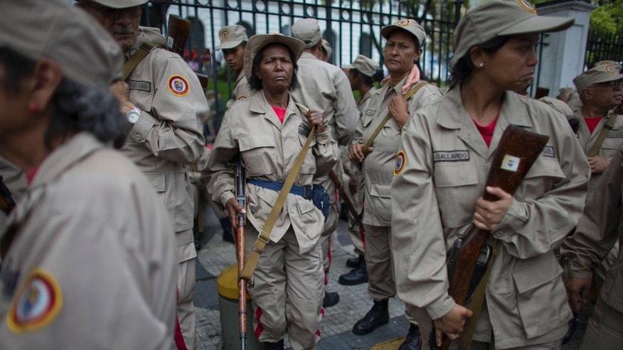 Members of the Bolivarian Militia participate in their seventh anniversary celebration, in front of the Miraflores presidential palace in Caracas, Venezuela, Monday, April 17, 2017. Officially known as the Venezuelan National Bolivarian Militia, it is a branch of the National Armed Forces of Venezuela created by the late President Hugo Chavez. The anniversary celebration took place with unrest spreading in Venezuela as confrontations between opposition demonstrators and authorities continue. (AP Photo/Ariana Cubillos)
