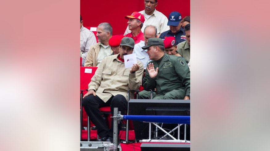 Venezuelan President Nicolas Maduro, left, speaks to Defense Minister Padrino Lopez during the seventh anniversary celebration of the Bolivarian Militia, in front of the Miraflores presidential palace in Caracas, Venezuela, Monday, April 17, 2017. Officially known as the Venezuelan National Bolivarian Militia, it is a branch of the National Armed Forces of Venezuela created by the late President Hugo Chavez. The anniversary celebration took place with unrest spreading in Venezuela as confrontations between opposition demonstrators and authorities continue. (AP Photo/Ariana Cubillos)