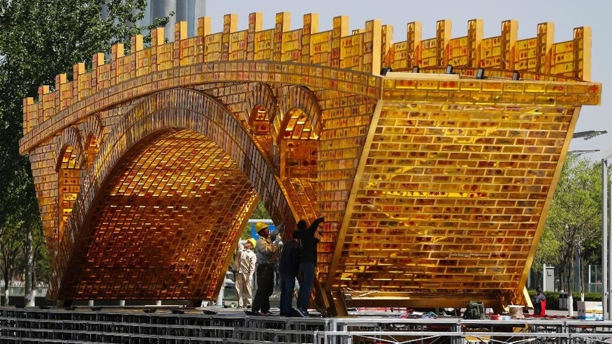 "Workers install wires on a 'Golden Bridge of Silk Road' structure on a platform outside the National Convention Center, the venue which will hold the Belt and Road Forum for International Cooperation, in Beijing, April 18, 2017. Leaders of 28 countries are set to attend the Chinese summit showcasing President Xi Jinping's signature foreign policy plan, but few will hail from major Western countries. Chinese foreign minister Wang Yi said Tuesday that Vladmir Putin of Russia, Recep Tayyip Erdogan of Turkey and Spain's Mariano Rajoy are among those slated to appear next month in Beijing for a summit to discuss Xi's ""One Belt, One Road"" infrastructure investment program to stitch together the Eurasian continent. (AP Photo/Andy Wong)"