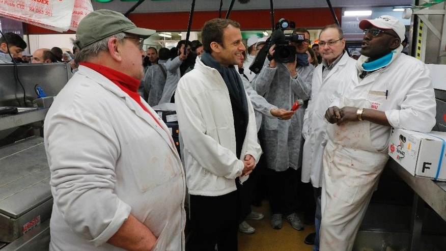 French presidential candidate Emmanuel Macron, second left, talks with butchers as he visits the meat pavilIon at the Rungis wholesale food market, south of Paris, Tuesday April 18, 2017. Macron, an independent centrist with pro-business, pro-European views, is among the front-runners in France's unpredictable presidential race. The top two vote-getters in the first round Sunday will advance to the May 7 presidential runoff. (Philippe Wojazer; Pool via AP)
